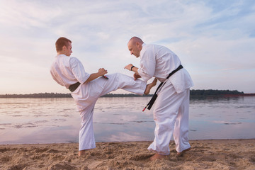 two karate men fight on the beach near river