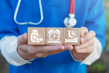 Doctor holds wooden cubes with insomnia icons. Insomnia Disease Health Care concept.