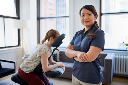 portrait of a Chinese woman massage therapist giving a neck and back pressure treatment to an attractive blond client at her workplace in a bright office