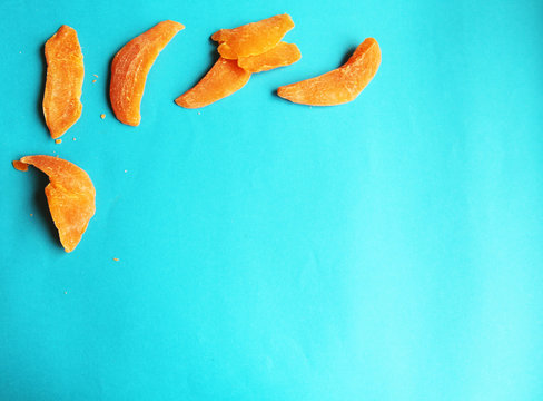dried fruits mango orange slice on blue bright background. Tasty yummy dieting