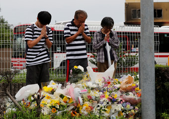 People pray in front of a row bouquets placed out for victims of the torched Kyoto Animation building in Kyoto