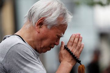 A man prays for victims of the torched Kyoto Animation building in Kyoto