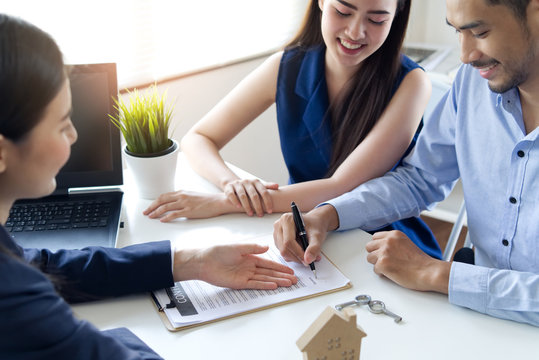 Young Asian couple making contract with house sale agency. Man signing the contract and his wife sitting next to him looking the contract document with smile. Real estate agreement successful concept.