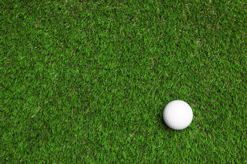 Golf ball on green artificial grass, top view with space for text