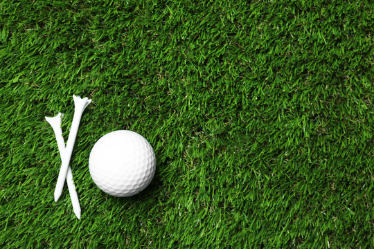 Golf ball and tees on artificial grass, top view with space for text