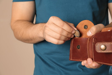Young man putting coin into wallet on beige background, closeup. Space for text