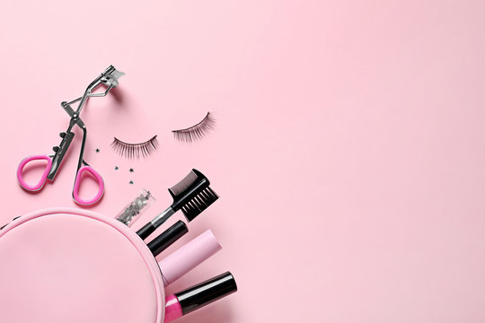 Flat lay composition with false eyelashes and makeup bag on pink background, space for text