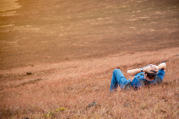 The man relaxing on outdoor. Lying down in sawanna area. Feeling relaxing.