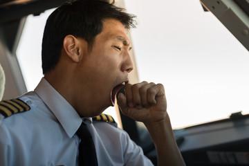 Tired man yawning at work. Pilot flying airplane. Wall mural