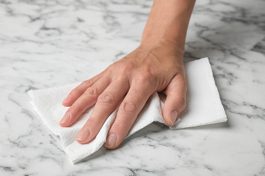 Woman wiping marble table with paper towel, closeup