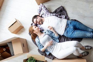 Young couple lying at the floor in empty room with unpacked boxes all arround