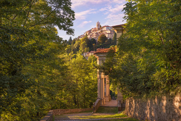 Old and famous Italian medieval village. Sacro Monte of Varese with the holy road that leads to medieval village (in the background), with the eleventh chapel. World Heritage Site – Unesco