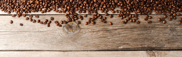 Overhead shot of roasted coffee beans on wooden background. Wall mural