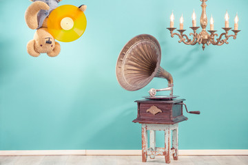 Retro Teddy Bear toy hanging down its head with LP vinyl in paws, antique gramophone phonograph, old bronze chandelier front blue background. Nostalgia music concept. Vintage style filtered photo