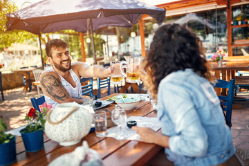 Beautiful couple sitting in a restaurant enjoying in beer and conversation.