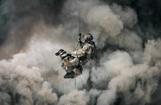 Military soldier with dog roping helicopter between mist and smoke