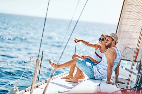 Romantic man and woman spending time together and relaxing on yacht.