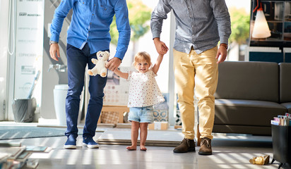 gay couple with child in store for household.