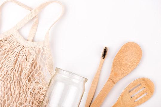 Zero waste eco friendly flat lay. White background. Mesh shopping bag, mason jar, bamboo toothbrush