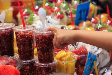 Hand pointing glass full of fresh fruit, put on the market of La Boqueria, an old traditional market in Barcelona, famous monument.