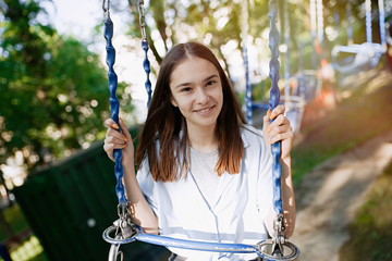 Poster Attraction parc Happy child teenage girl riding chain carousel swing at amusement park