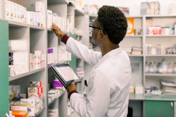 Poster Apotheek African American male pharmacist using digital tablet during inventory in pharmacy.