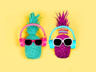 Pineapples in headphones and glasses on a yellow background