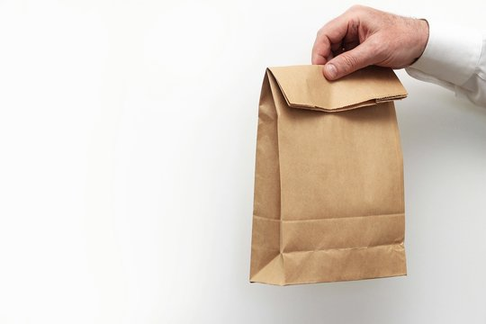 Close up male holds in hand clear empty blank craft paper bag for takeaway isolated on white background. Packaging template mock up. Delivery service concept. Copy space.