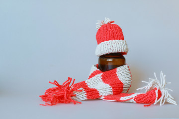 a bottle of syrup dressed in a scarf and cap in the season of colds