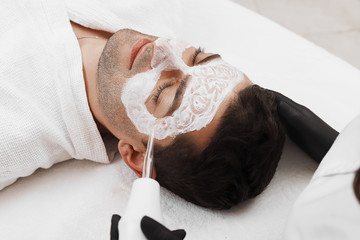 Face of beauty clinic customer. Man having darsonval therapy.