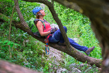 Woman mountaineer with a blue helmet resting on a tree branch, in Tureni-Copaceni gorge, Romania. Her climbing gear (belay tube, prusik loop, carabiners, sewn sling) hangs down from her harness.