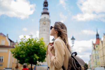 Woman in sunglasses and backpack in aged city center square. Poland