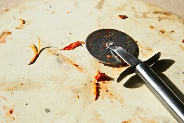 A pizza cutter on a baking tile. Junk food or fatty food concept image.