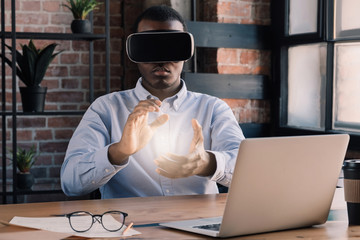 VR science concept. African engineer using virtual reality technology with laptop in modern office