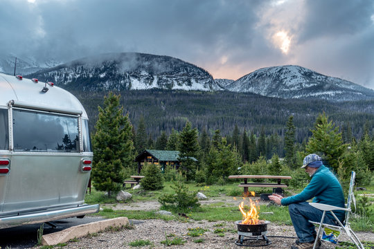 A camper warming his hands at the campfire, Timber Creek Campground, Rocky Mountain National Park