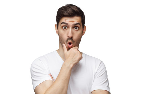 Young surprised man with eyes wide open, holding his chin, surprised with news, isolated on white background