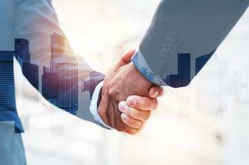 Welcome. double exposure image of investor business man shaking hands with partner for successful meeting deal with during sunrise and cityscape background, investment, partnership, teamwork concept