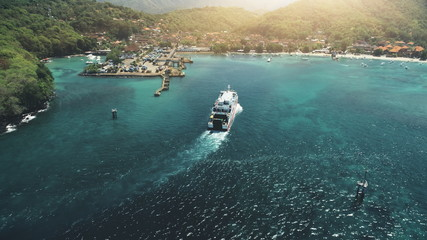 Aerial View: Ferry sailing in harbor. Travel Vacation Recreation Paradise Tourism. Sunset mountain hills in background. Beautiful nature landscape in Tropical Bali Island. Cinematic filter
