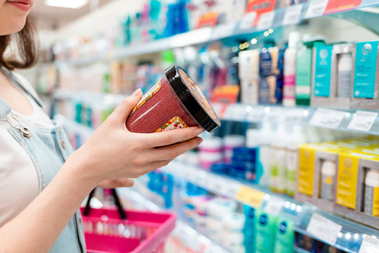 Shopping. The woman is holding a body cream. A jar of cream and hands close-up