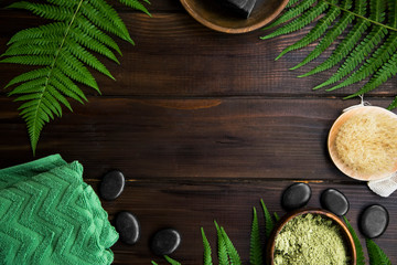 Green spa top view setting with fern leaves on wooden background with copy space, massage stones, green towel, clay powder