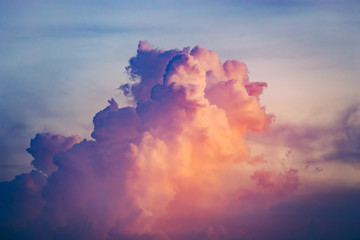 Close-up colorful clouds going up in sunset sky. Natural phenomena. Atmospheric environment. Splash of rose, scarlet and blue tints. Great background for different kinds of collages and illustrations.