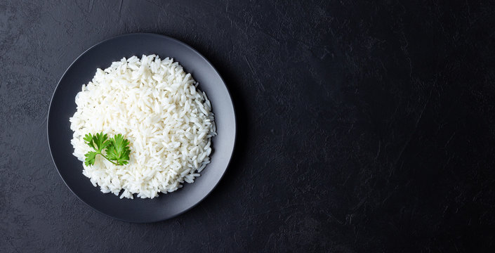 Steamed rice on black plate. Black stone background. Top view with copy space.