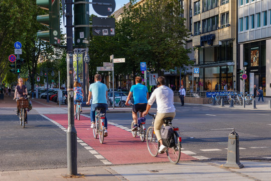 People or cyclists ride bicycle on the bicycle lanes cross at pedestrian crossing at Königsallee in Düsseldorf, Germany. Urban Eco friendly lifestyle transportation.