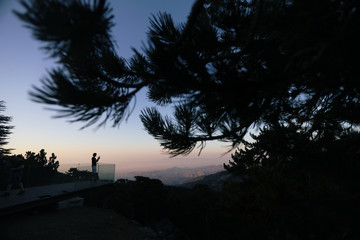 A tourist takes a photograph from an observation point in Troodos Mountain
