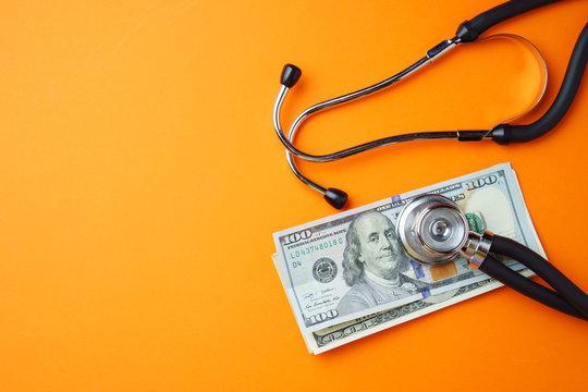 Medical stethoscope and money on orange background