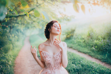 charming goddess of the spring forest stands on a narrow path and breathes in the sweet smell of nature, pleasure in motion, lady with her eyes closed strokes her beautiful neck with her fingertips