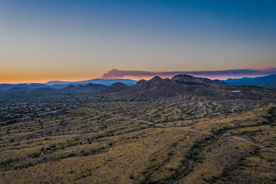 Wild fire smoke viewed from a drone as the smoke rises and catches the evening light of the setting sun.