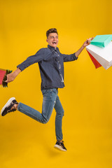 Aluminium Prints Superheroes Impressed young man with colorful shopping bags in hands with open mouth, happy after successful shoping, isolated over yellow background