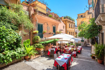 Street view with cafe in old town Taormina. Sicily, Italy