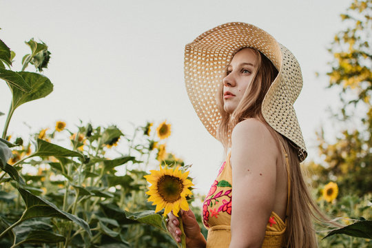 Slow Living concept New Lifestyle Trend. Relaxing young woman with lowers in nature, in corn, sunflower field